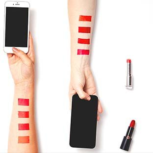 Image of hands holding mobile and phones and having tested lipsticks on their arms